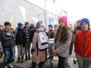 Barn står och väntar utanför en stor byggnad.