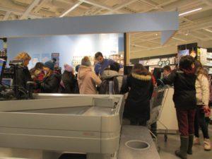 Flera barn står vid kassan i en butik.