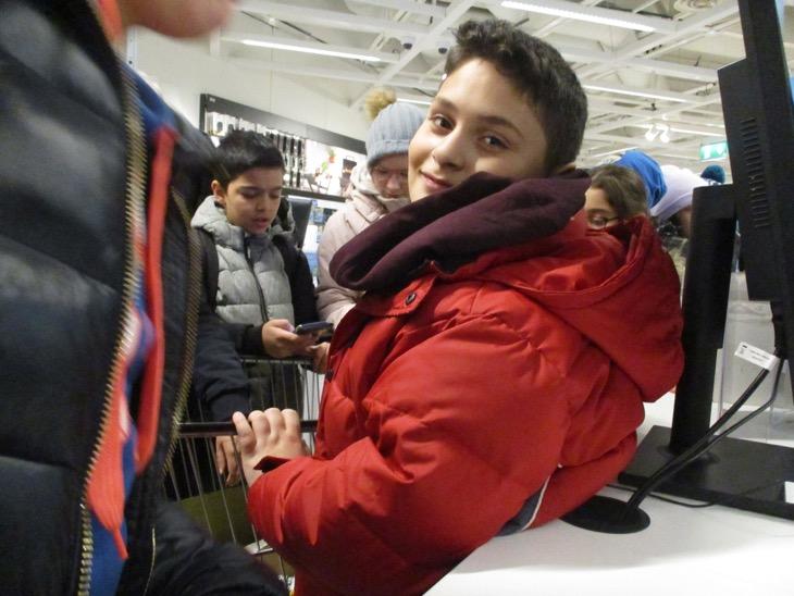 Ett barn i röd jacka tittar in i kameran.