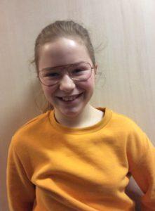 Bild på person men orange tröja och glasögon.