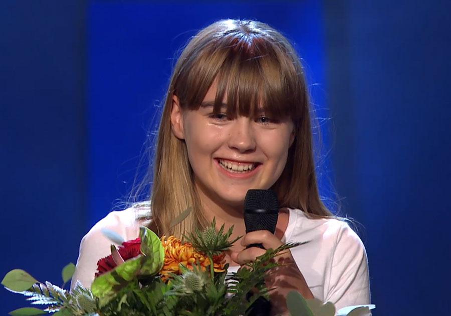 Paula håller en blombukett och en mikrofon.
