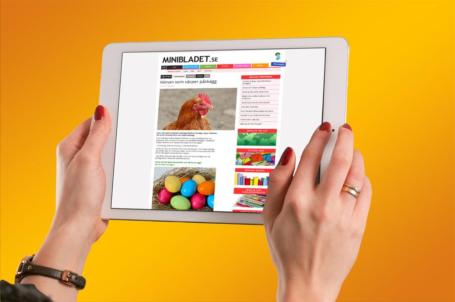 Två händer som håller i en surfplatta mot en gul bakgrund. På skärmen syns en MiniBladetartikel.