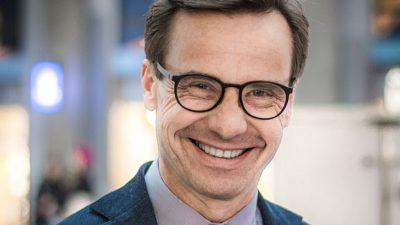 Ulf Kristersson har glasögon, kort hår och en kostym. Han har en del rynkor runt ögonen som syns extra mycket eftersom han ler stort.