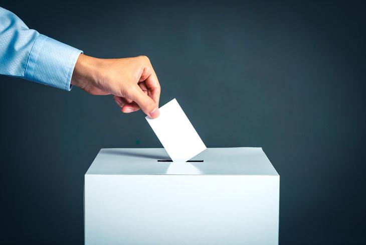 En hand stoppar ner ett papper i en skår på ovansidan av en låda.
