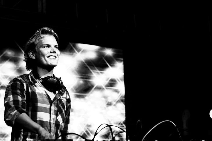 Avicii står bakom ett mixerbord. Han har en rutig skjorta och halvlångt hår som är struket bakåt. Han tittar ut mot publiken och ler.