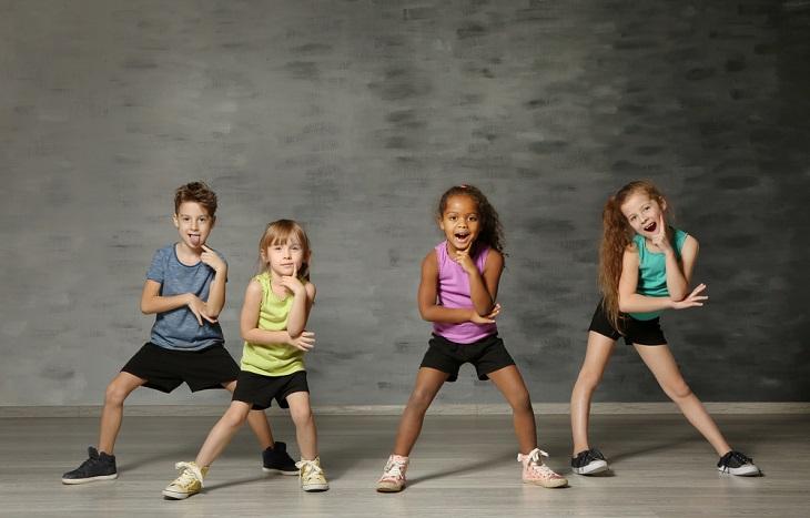 Fyra barn står uppställda i shorts och kortärmat. De står med benen brett isär, böjda knän och håller ett finger på kinden. De ser ut att vara mitt i en dans, eller precis har avslutat en.