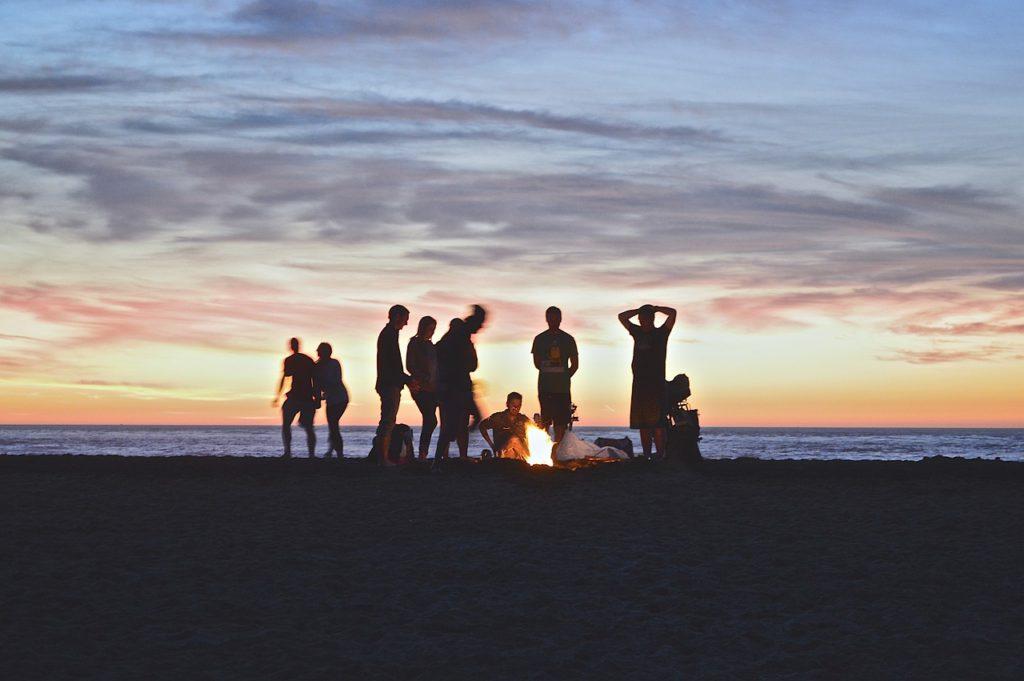 En strand med en eld. Runt elden har några personer samlats och tittar ner på den lilla elden.