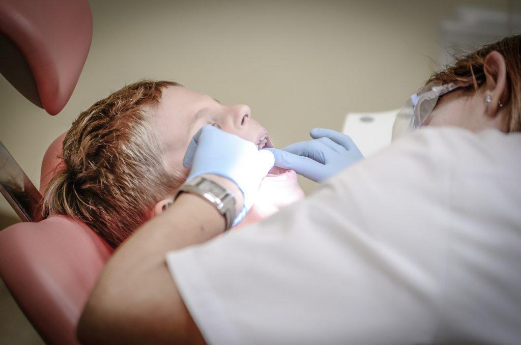 En pojke blir undersökt av en tandläkare med ljusblå handskar