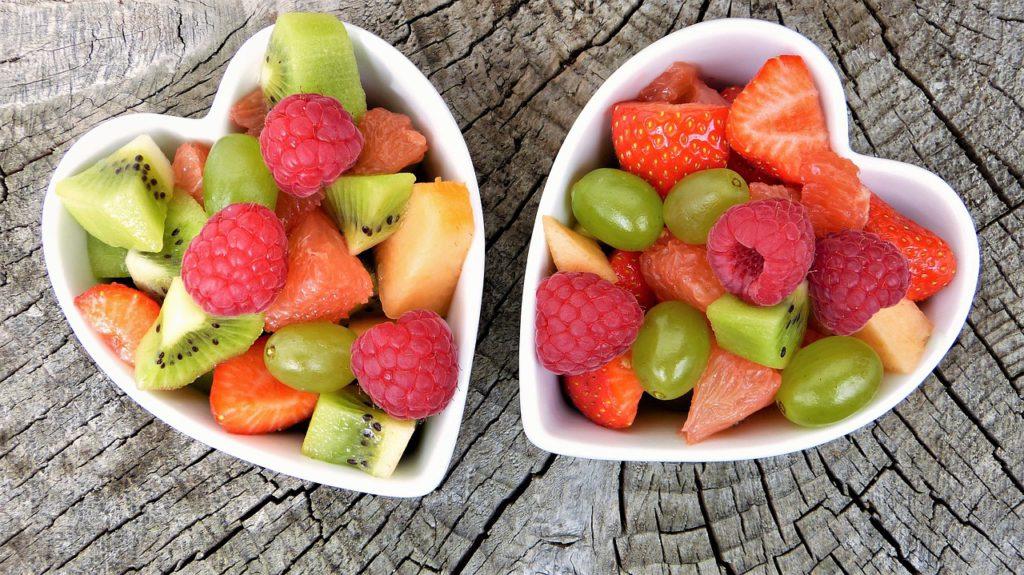 Två skålar med frukt. Skålarna är hjärtformade. Det är vindruvor, jordgubbar, hallon, kiwi och apelsin i skålarna.
