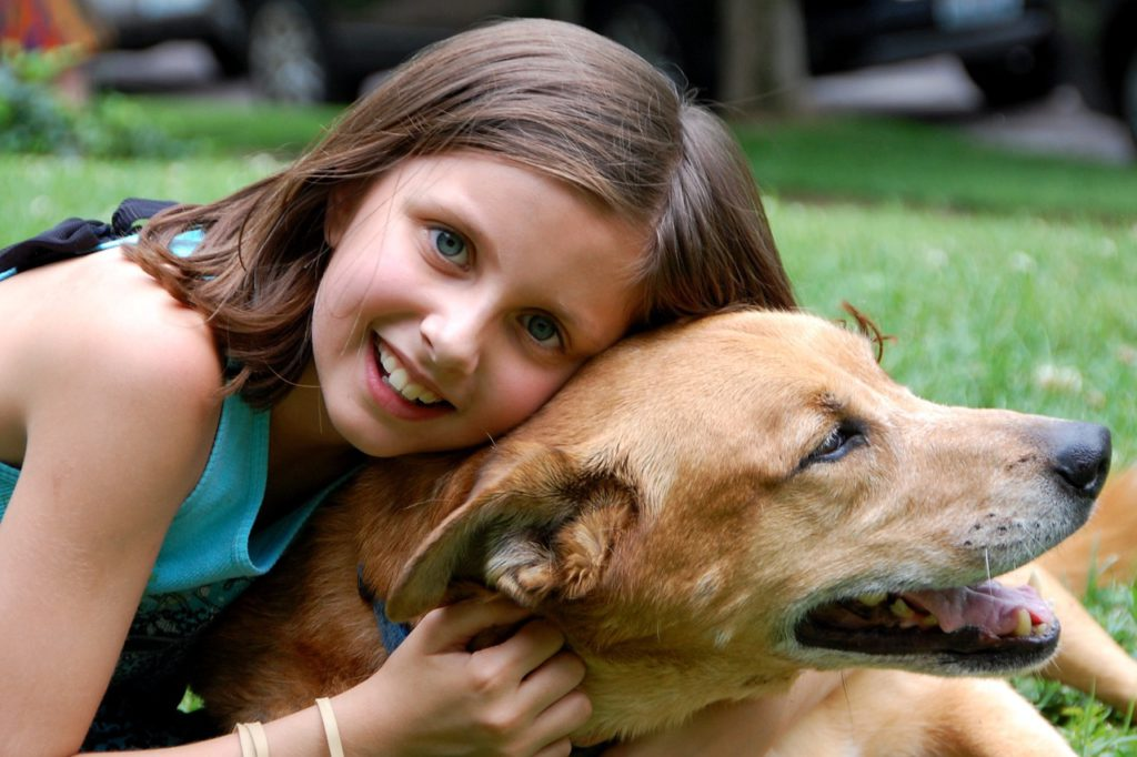 Ett barn med brunt hår som kramar en guldig hund