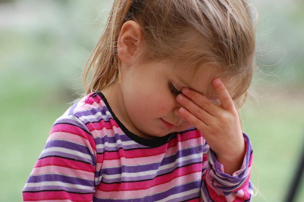 Ett litet barn sitter med huvudet i handen. Barnet har långt hår i en tofs och en randig tröja.