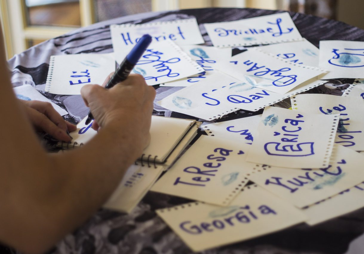 En hand som skriver med blå tuschpenna i ett anteckningsblock . På bordet ligger lappar med olika namn utspridda.