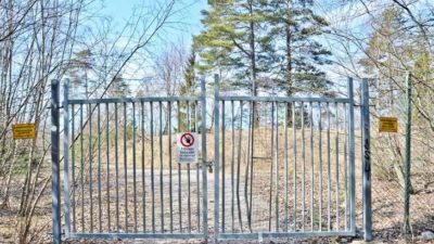 En grind och ett staket med skyltar som säger att det är förbjudet att gå in. Innanför grinden står träd vid sidan om en grusväg.