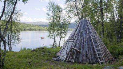 En kåta står i skogen intill en sjö. Kåtan ser ut som ett spetsigt tält, men gjort av trä.