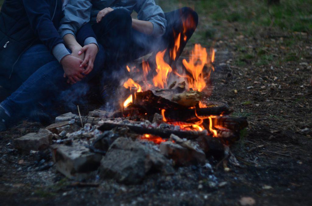En eld på en eldstad av sten. Intill elden sitter några personer och håller om varandras ben.