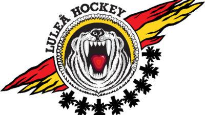 En vit tiger ryter. En kan se dess stora tänder och röda tunga. Tigern är en i en cirkel och runt cirkeln syns fägerna rött, svart och gult.