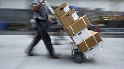 En person går med en vagn framför sig. Vagnen är lastad med lådor som är staplade på varandra.