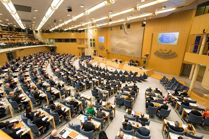 Ett stort rum fyllt av stolar med varsin bänk framför. Stolarna är formade i en halvcirkel. Framför stolarna är en slags scen där det står flera långa bord och som har en stor skärm bakom sig.