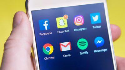 En hand håller i en mobil. På skärmen är det flera ikoner för olika appar. En av dem är Snapchat. Vid Snapchat-ikonen är det en röd liten etta som betyder att det har kommit en ny snap.