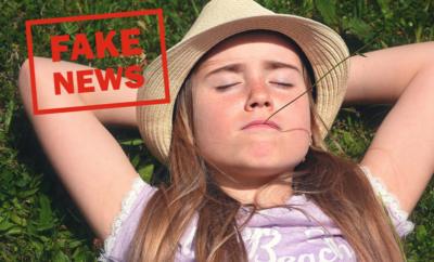 """En flicka som ligger på rygg i gräs och texten """"Fake News"""" skriven med röda bokstäver."""