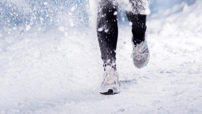 Ett par fötter och ben. De har löparskor och springer i snö som yr.