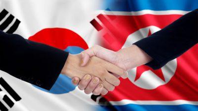 Båda ländernas flaggor. Den ena har cirkel i mitten som är hälften blå och hälften röd. Den andra har en stora röd stjärna i mitten. Framför flaggorna är det två händer som skakar hand.