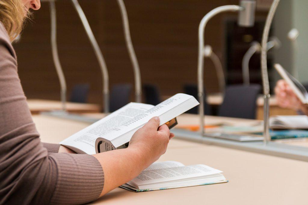 En elev sitter och läser i en bok