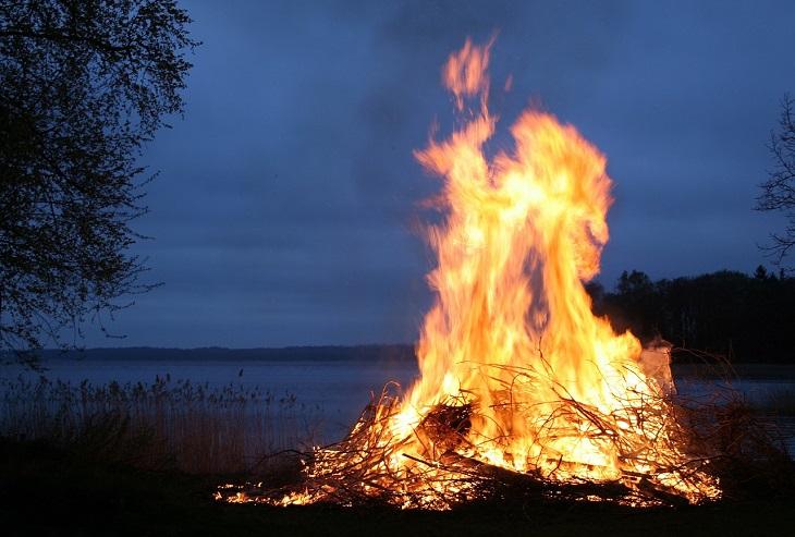 En stor brasa brinner i mörker, vid en sjö.