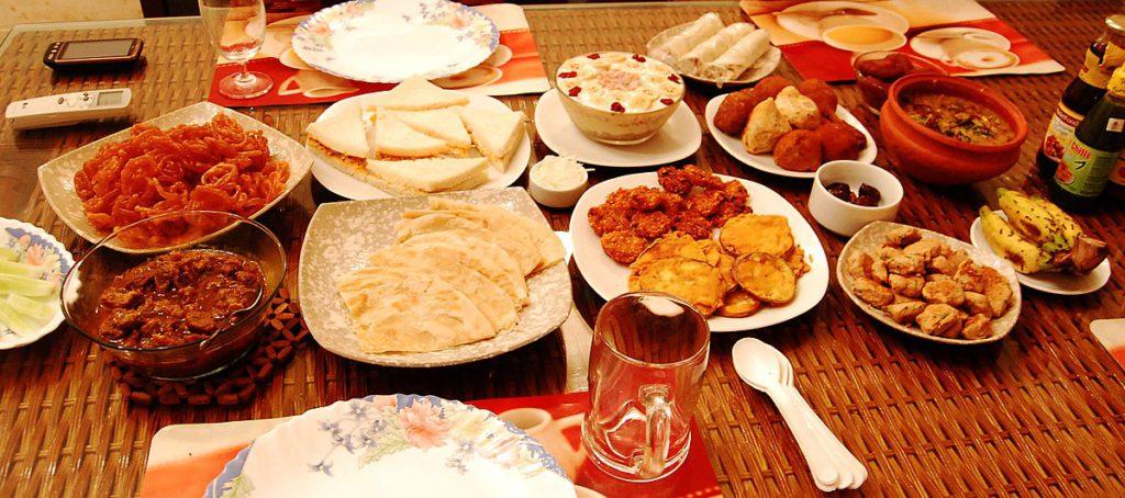 Ett bord med många tallrikar fyllda med mat. Det finns bröd, grytor, plättar rullar och mycket mer.