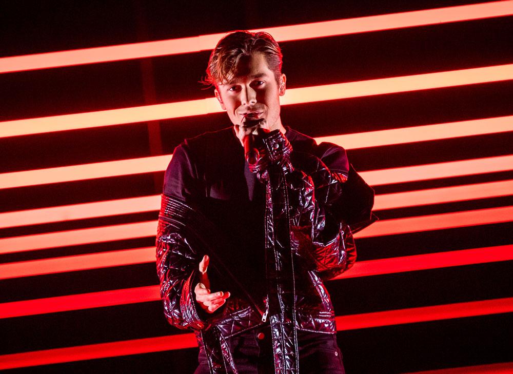 Benjamin har på sig svarta kläder. Han håller i en mikrofon. I bakgrunden lyser röda lampor.
