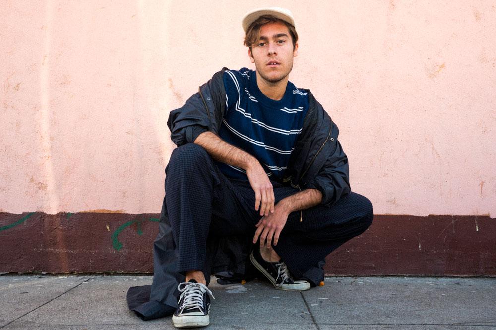 Benjamin sitter på huk framför en ljusrosa vägg. Han har på sig blå kläder och en vit keps.