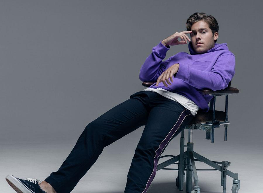 Benjamin sitter tillbakalutad på en stol. Han har en lila huvtröja och blå träningsbyxor på sig.