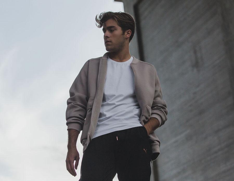 Benjamin står bredvid en grå byggnad. Han har svarta byxor, en vit tröja och en beige jacka på sig.