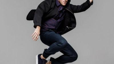 Benjamin hoppar upp i luften. Han har blå jeans, rutig skjorta och en svart jacka på sig.