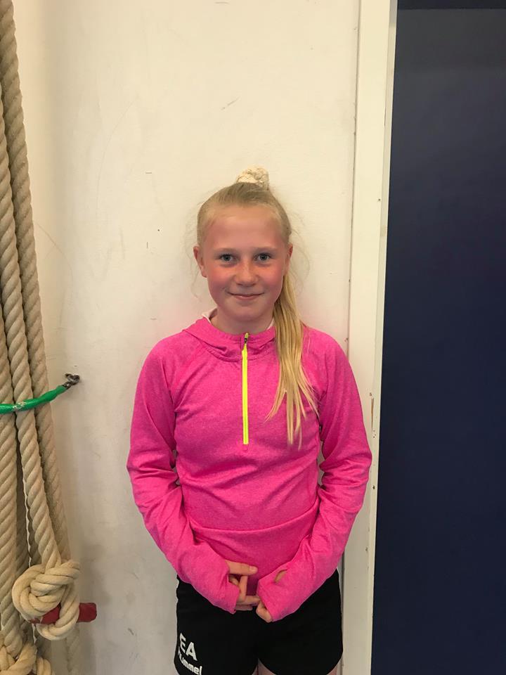 Emilia står framför en vägg i en gympasal. Hon har långt hår uppsatt i en hästsvans. Hon har shorts och en sporttröja på sig.