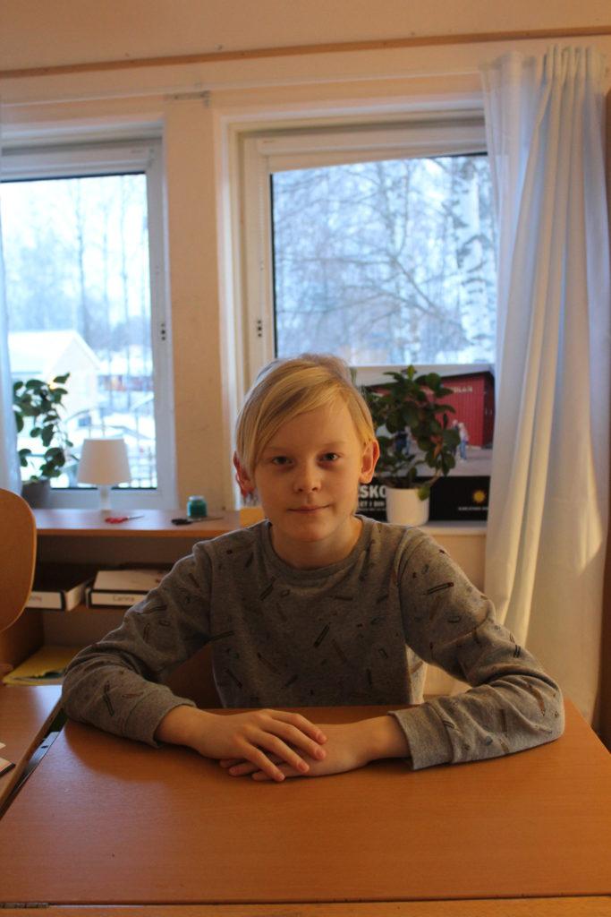 Olivers sitter bakom en skolbänk. Han har långärmad tröja och blont hår med lugg som ligger åt sidan. Han tittar bestämt in i kameran.