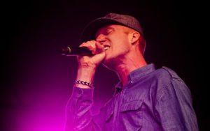 Artisten står på scen och sjunger i en mick.