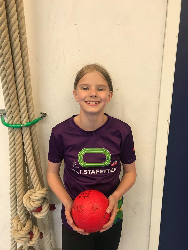 Saga står framför en vägg i en gympasal. Hon håller i en handboll och ser glad ut. Hon har långt hår i en hästsvans och gluggar mellan tänderna.
