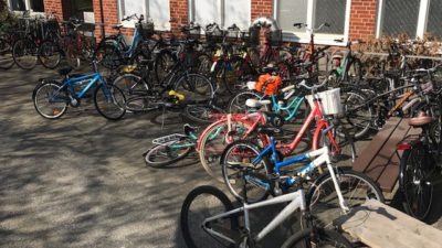 En cykelparkering intill en vägg som är helt full av cyklar som ligger välta på marken och många som står utanför cykelställen.