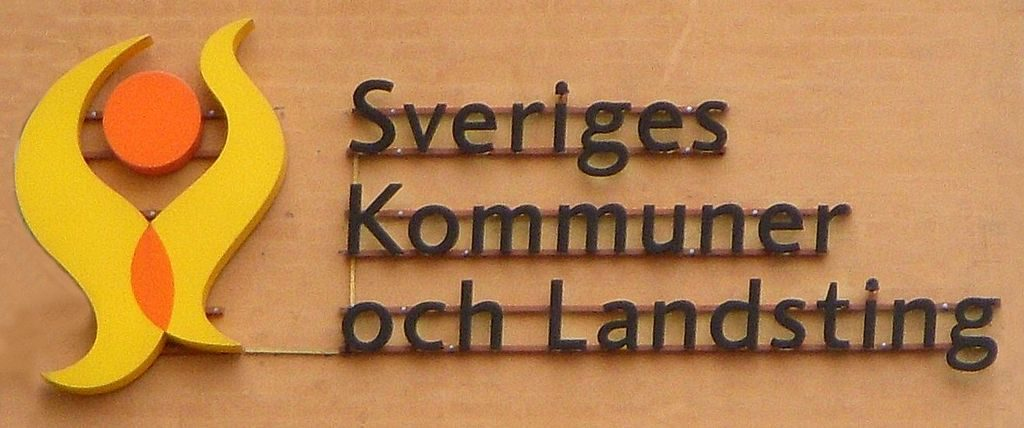 """En skylt med en gul och orange symbol som ser lite ut som en eldsflamma och lite som en gubbe. Bredvid står det """"Sveriges kommuner och landsting""""."""