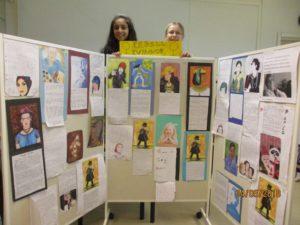 Två skolelever visar upp en vägg med uppsatta skolarbeten över historiska kvinnor under rubriken: Rebellkvinnor.