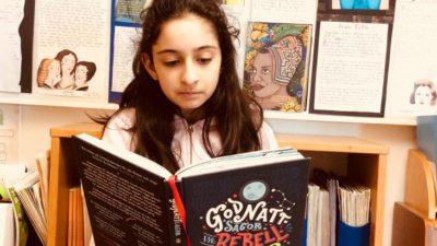 En skolelev sitter och läser i en bok med titeln: Godnattsagor till Rebelltjejer. I bakgrunden är en vägg med uppsatta skolarbeten över historiska kvinnor.