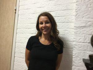 En person med långt brunt hår ler mot kameran framför en vit vägg.