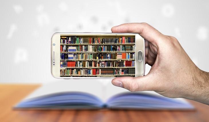 En hand håller upp en smartphone. På skärmen syns massa böcker i hyllor.