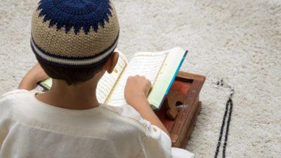 Ett barn sitter med ryggen mot oss. Framför sig har det en uppslagen koran på en bricka. Bredvid ligger ett ban med pärlor. Barnet har en virkad lite mössa på sig.