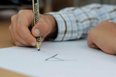 Händerna på ett barn. Ena handen håller i en penna och skriver bokstaven A på ett rutigt papper.