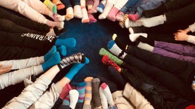 Barn sitter i ring med fötterna tillsammans. Strumporna har olika mönster och färger. Mattan under dem är mörkt blå.