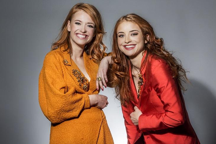 Clara och Henry ler stort mot kameran. Båda har långt svallaande hår och mycket smink. De håller i sina jackor så de ska vara stängda. De har stora glimrande stenar på sina jackor och många ringar.