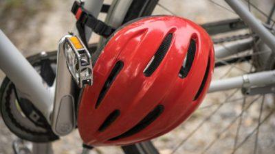 En hjälm sitter fasthängd runt ramen på en cykel.