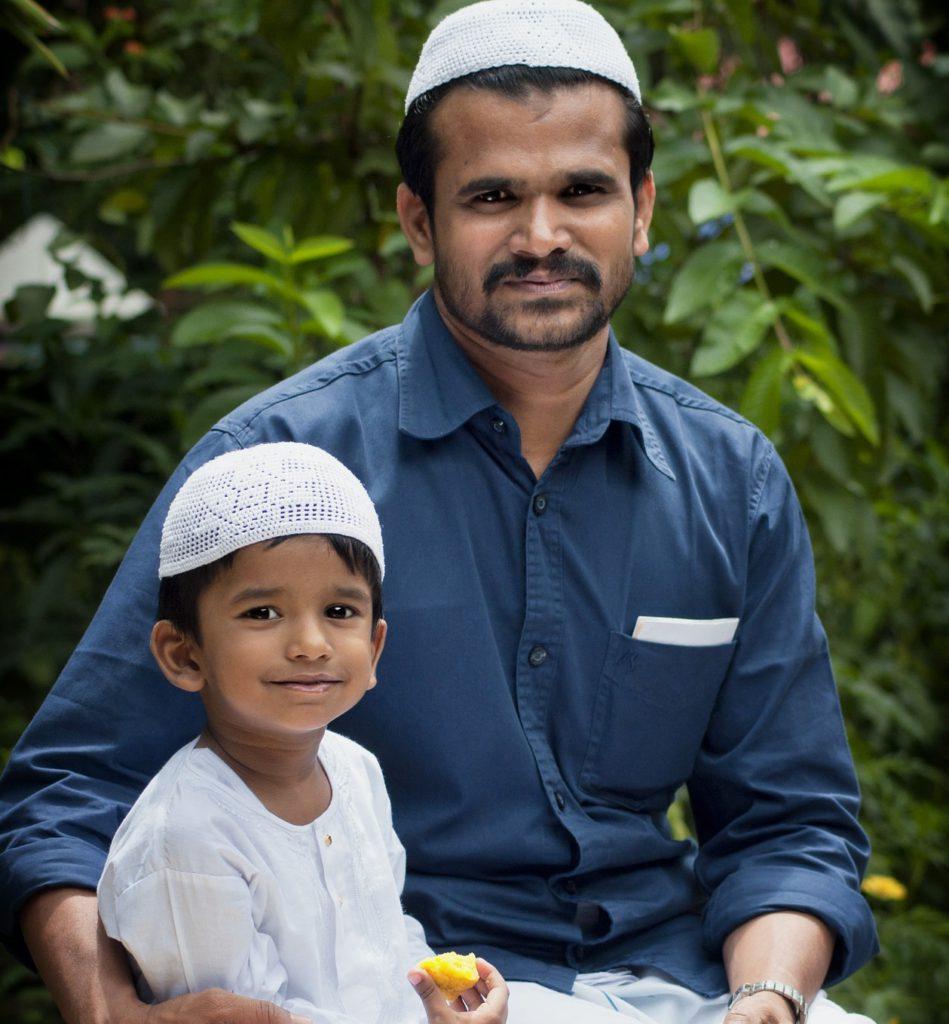 En pappa sitter och håller om sitt barn. Båda har vita små virkade mössor på sig. Barnet äter en bot frukt och ser glad ut.